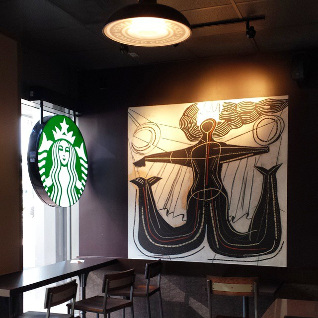 #Starbucks art. A bit meta, since both the art and the logo depict a two tailed #mermaid with a crown, and the two circular light sources in the piece resemble the circular light in the room and the logo itself. #coffee #coffeeshop
