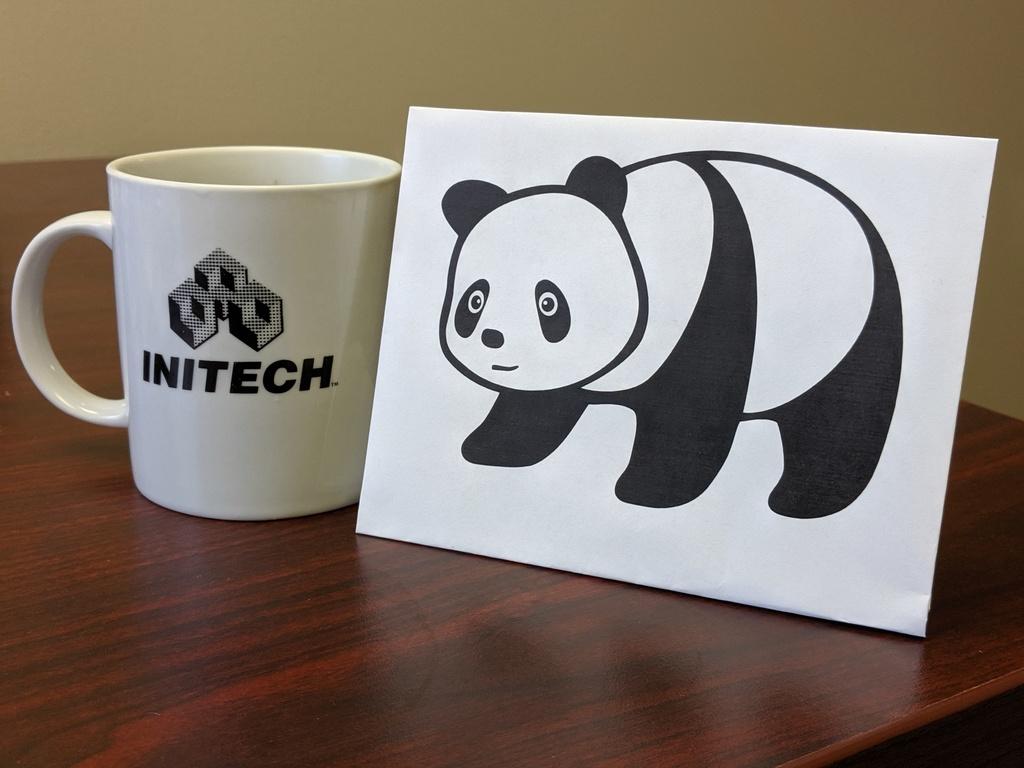 Paper panda next to an INITECH coffee mug.