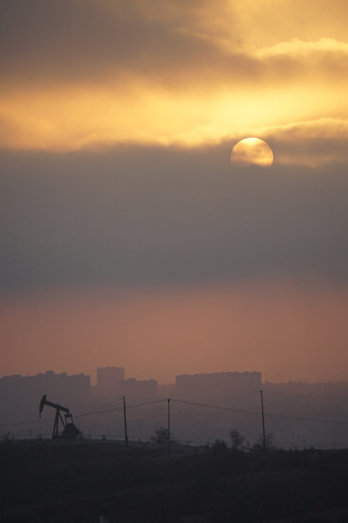 Sun setting behind clouds, above silhouettes of an oil pump and buildings.