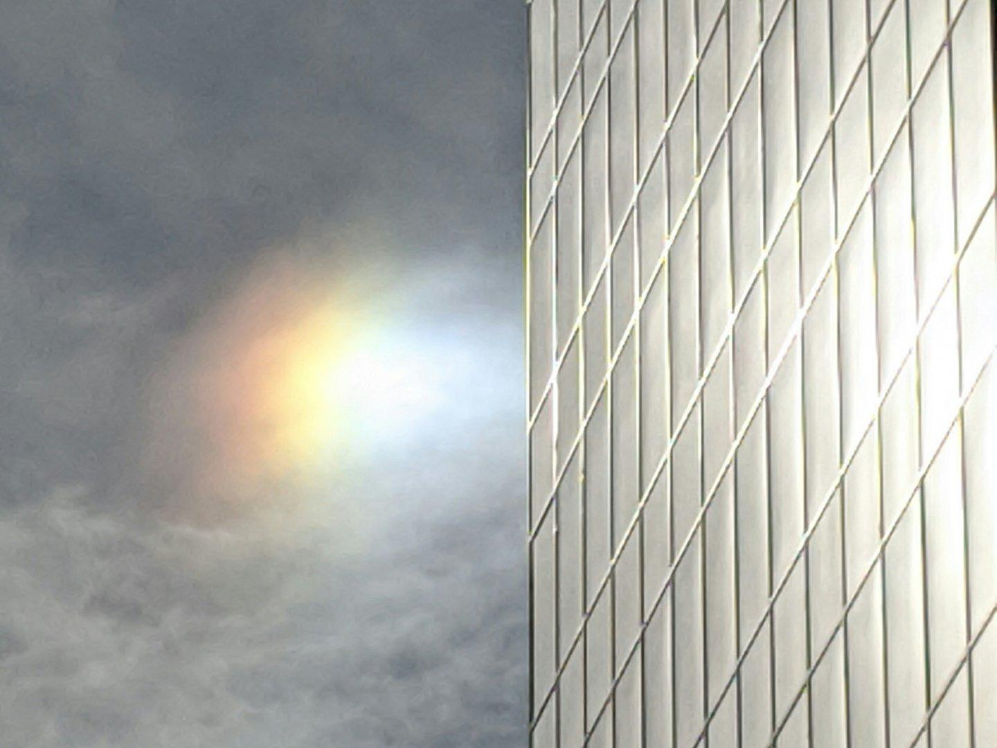 A bright #sundog next to a glass-sided building. The sun is off to the left out of frame. The sundog had a bit more color and more of the spectrum in it as seen through my polarized sunglasses, so I kind of wish I'd taken a shot through one of the lenses, but at least you can see how bright it was. I haven't adjusted the color on this image at all - except for cropping, it's straight out of my phone. #sky #halo