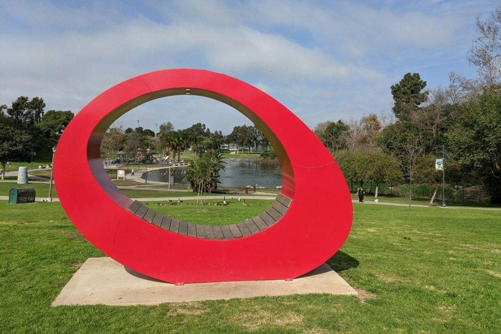 A red round asymmetrical gate sculpture in a park.