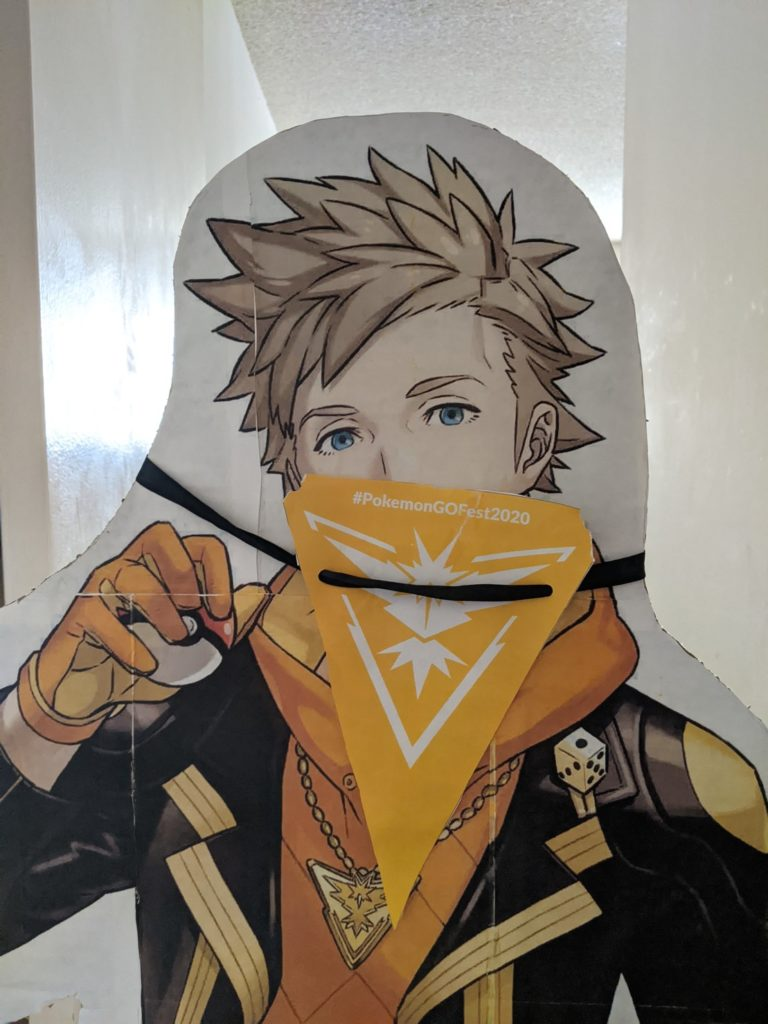 Head and shoulders of a cardboard cutout of Spark (Pokemon Go) with a pennant covering his mouth and nose like a bandana.