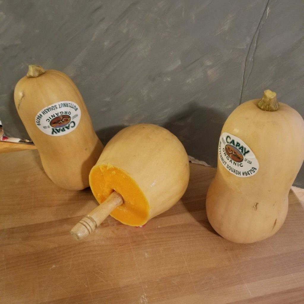 Three butternut squashes with white ovals on the smaller part. One is cut in half with a wooden rod sticking out of it.