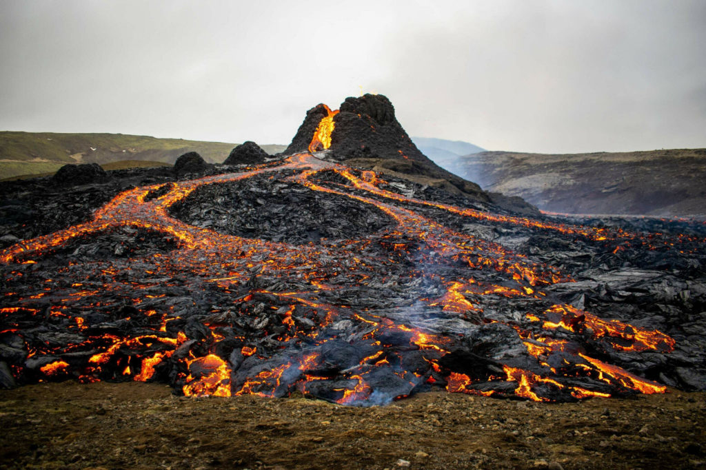 Steep volcano on rolling barren hills with streams of lava