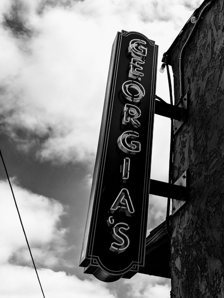 Vertical neon sign attached to the side of a building, labeled GEORGIA'S, with clouds in the background. Black and white.