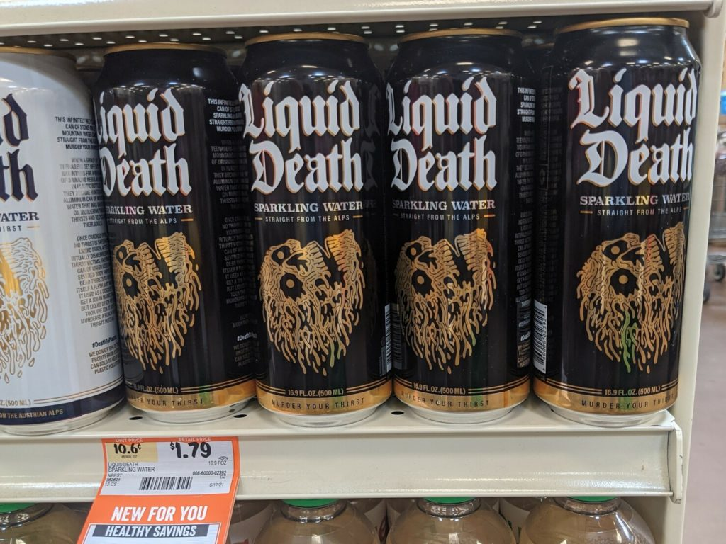 Drink cans on a shelf labeled Liquid Death in calligraphy with a flaming skull. The shelf has a price label with a discount labeled Healthy Savings.