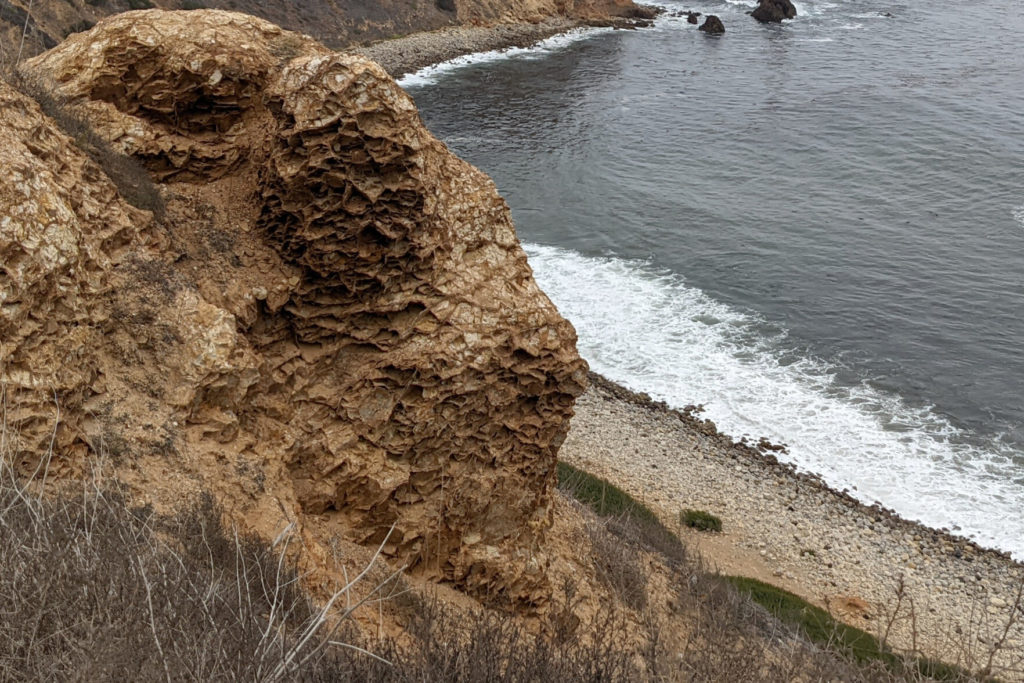 A large rock at the top of a cliff, looking down to the ocean, that looks like a stack of really thin layers that have been scrunched and folded and eroded differently.