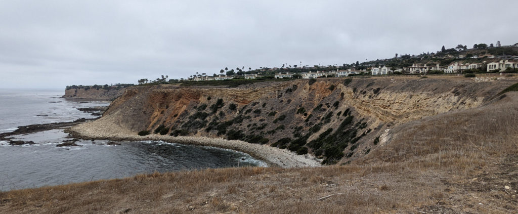 Looking across a cove with a narrow rocky beach from the top of the coastal bluffs on a gloomy day. Layers of stone curve upward in the middle, and bushes clump on the dirt escarpment. Houses line the hill in the distance.