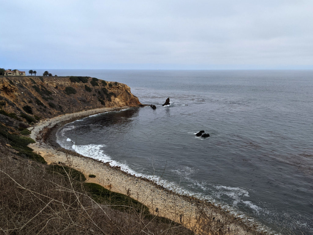 A cove on a gloomy day with rocky shore, high bluffs, and a few rocks out in the sea.
