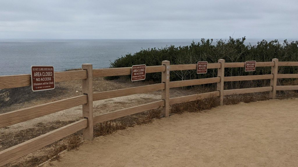 Fence along a trail near the ocean with Area Closed signs on every segment.
