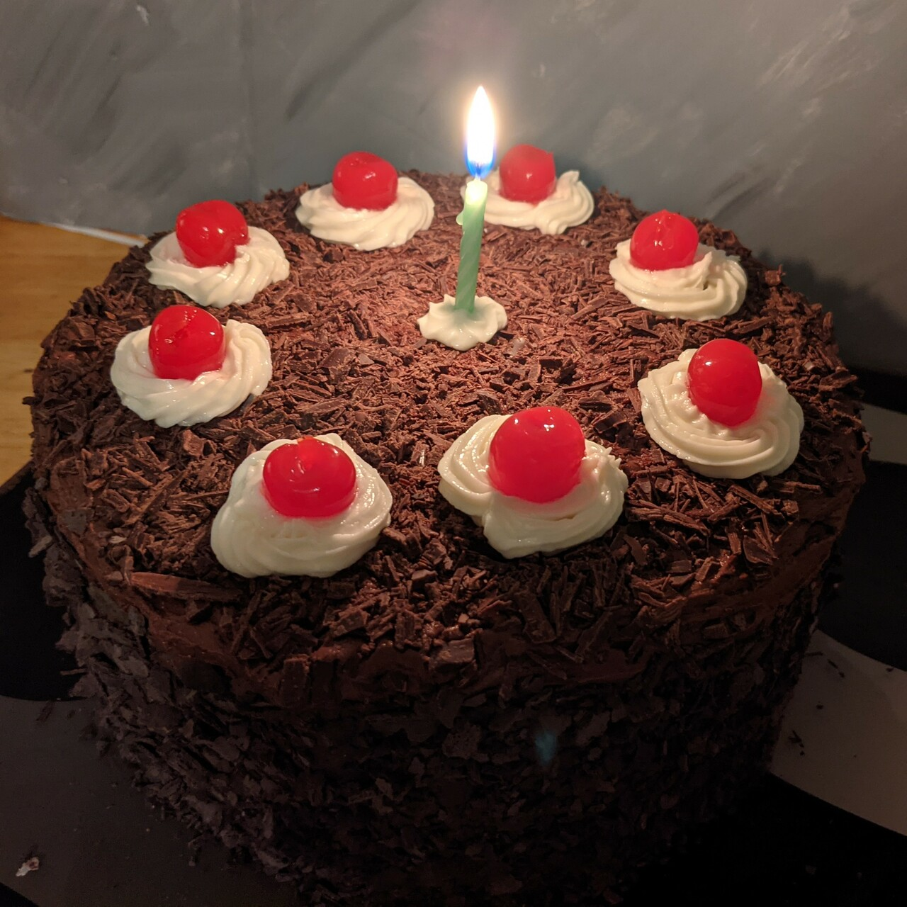 A chocolate cake with shavings on the sides and eight cherries spaced around the top, each embedded in whipped cream, with a single candle in the center.