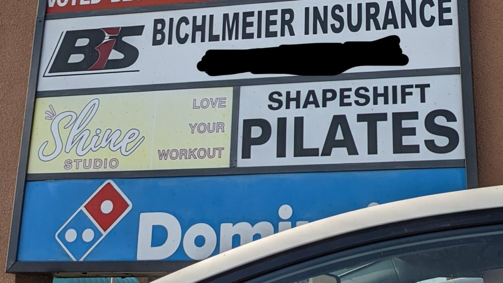 Store signs including Shapeshift Pilates